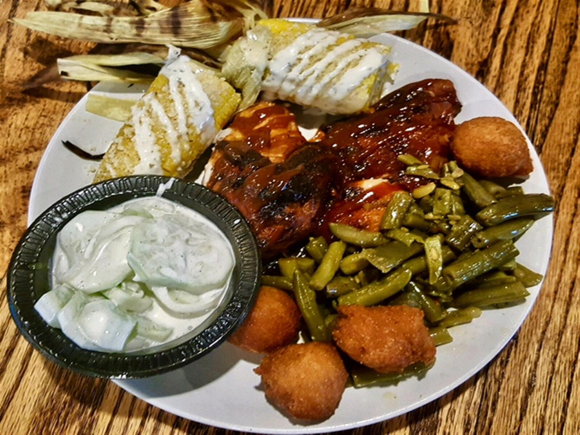 bbq chicken served with green beans, hush puppies and corn on the cobb