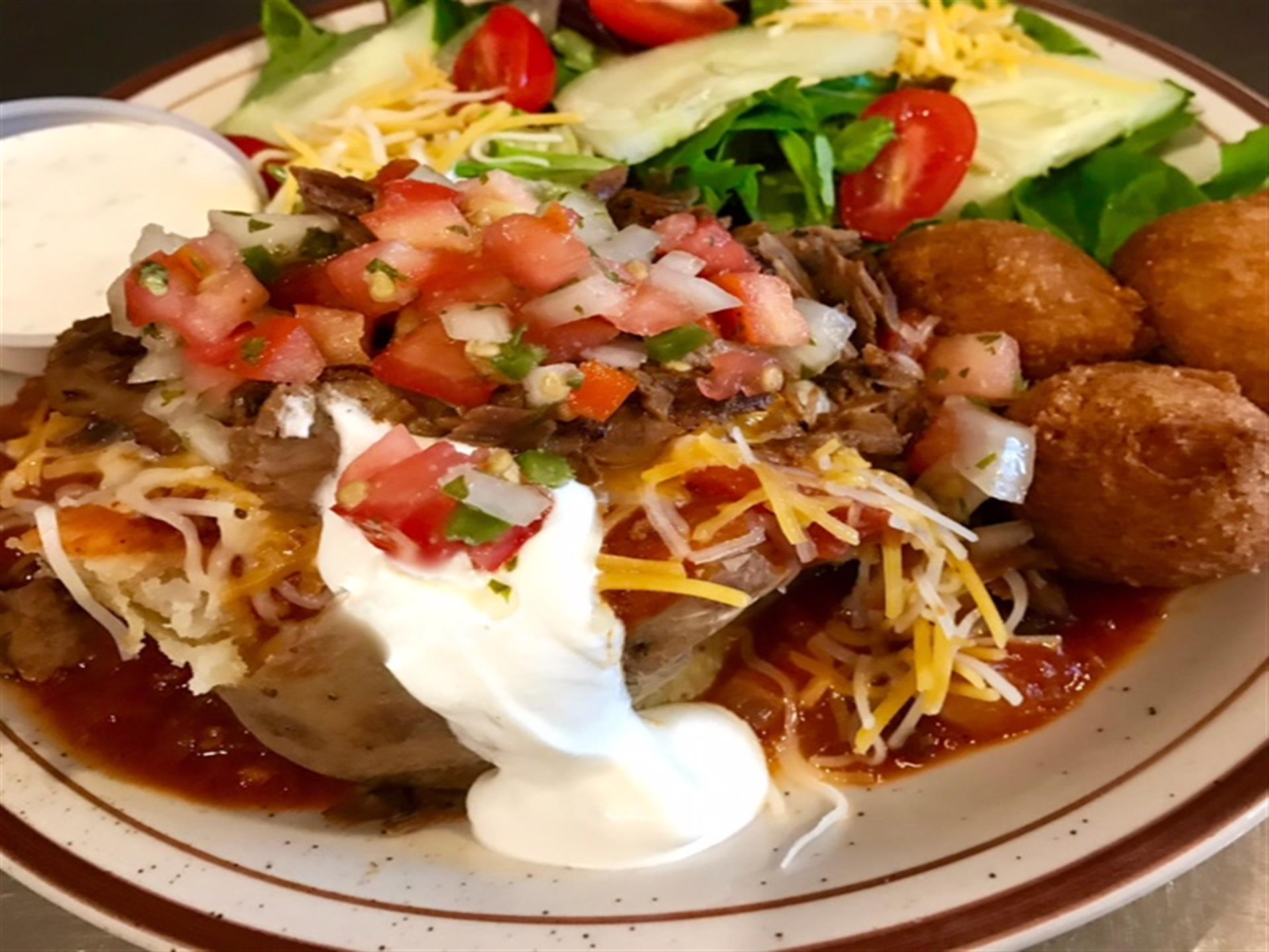 bbq baked potato served with side salad, and hush puppies