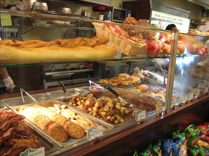 Display case showing variety of breads, bacon, potatoes, baked goods