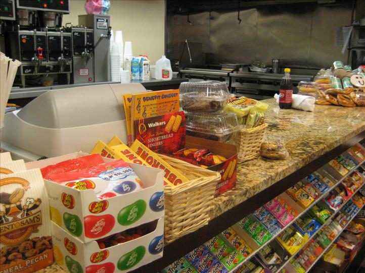 Various candies, gum, cookies at front counter with coffee machine in background