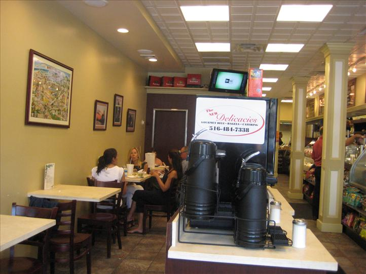 View of coffee machine in foreground with table of patrons in background