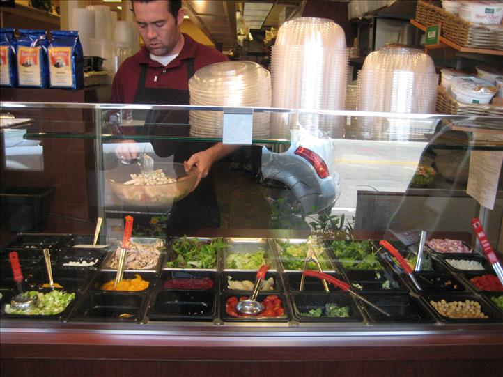 Worker preparing food behind salad bar station