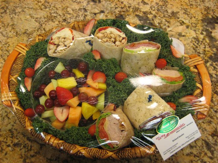 Wraps and fruits in a basket covered in palstic ready to be shipped for an event