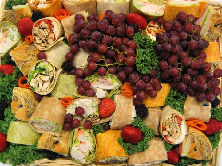 Wraps, fruits, and vegetables on a platter