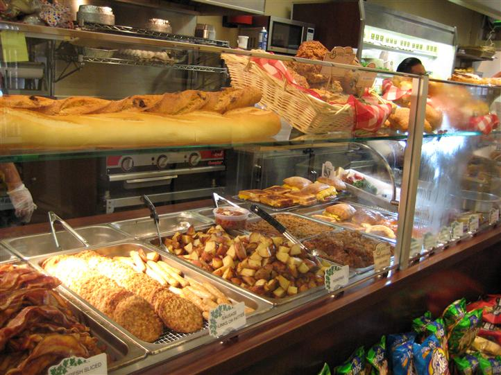 Multiple different foods on display behind a window at the deli area