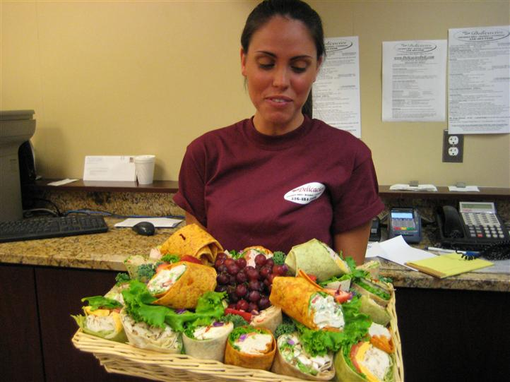 Lady holding a platter of multiple foods.