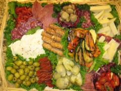 Multiple foods, meats, and cheese in a basket for a catering event
