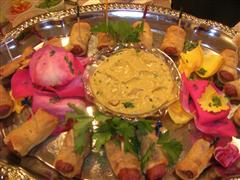 Wrapped hotdogs on a platter with flower garnish and dip