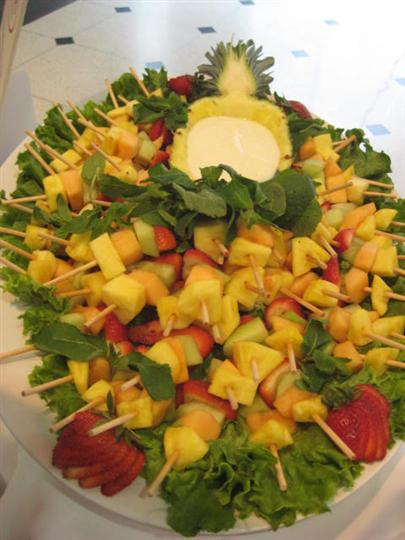 Fruit kababs on a platter topped on lettuce