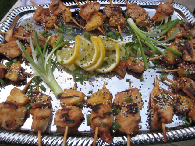 Mini kabab horderves on a platter with a flower and lemon garnish in the center
