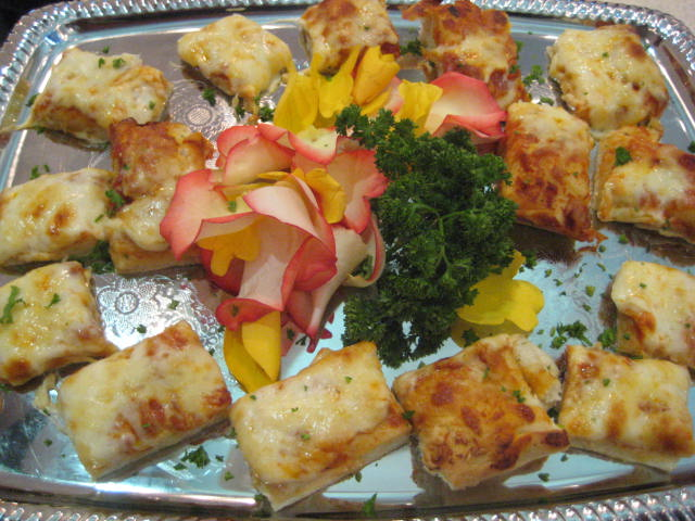 Horderves on a platter with a flower garnish in the center