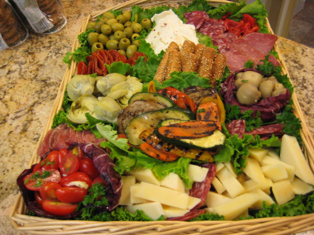 Basket filled with meats, cheeses, and vegetable