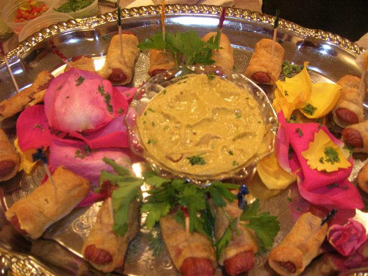 Hotdogs wrapped in dough with dip in the center on a platter