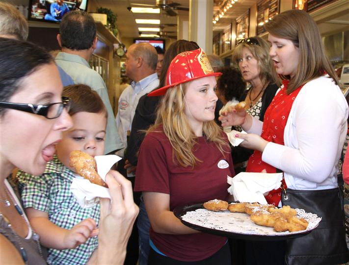 Waitress in fire fighter hat serving samples