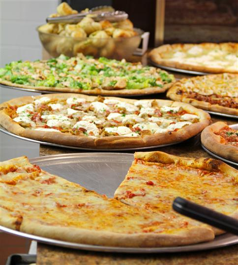Multiple different pizza pies on display