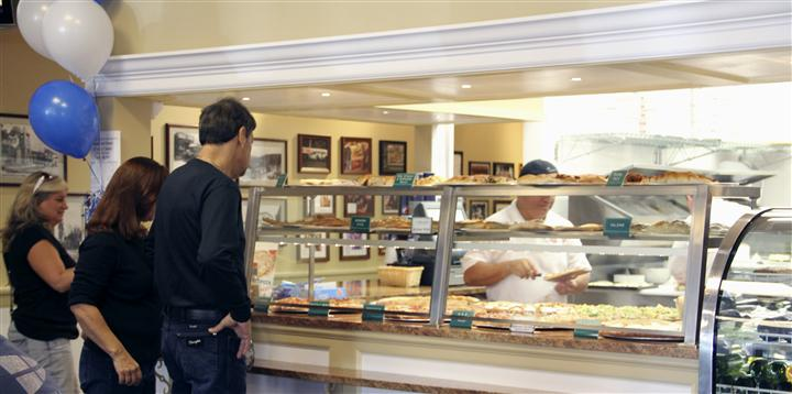 Man looking at pizza choices at counter