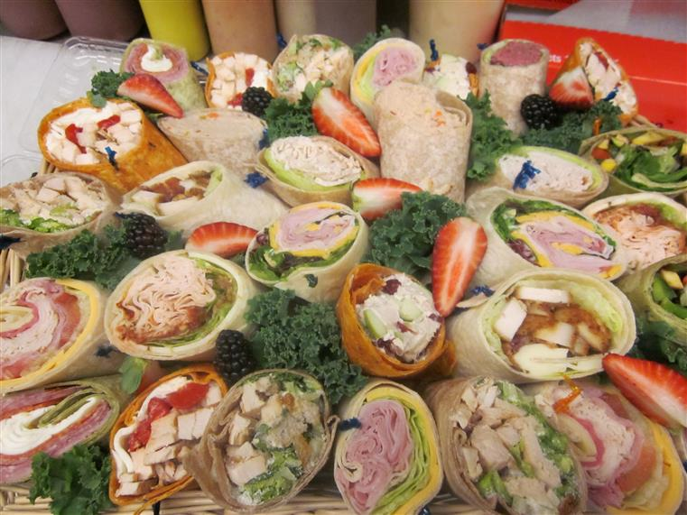 Catering platter of assorted wraps, sandwiches and sliced fruit