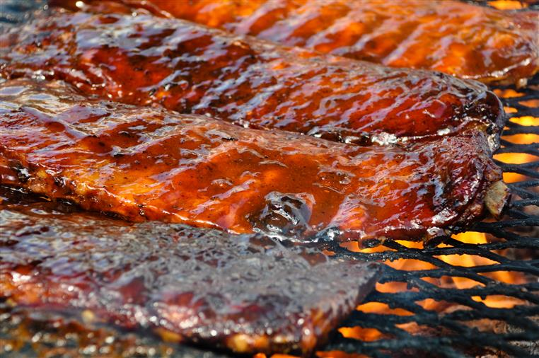 multiple bbq ribs on an open flame grill covered in bbq sauce