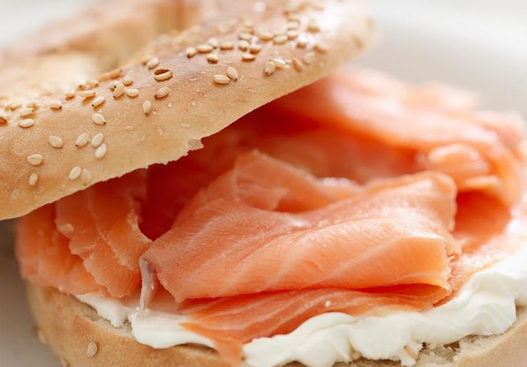 sesame bagel topped with cream cheese and lox