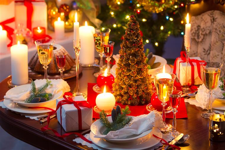 Table with Christmas decorations and plate settings with glasses