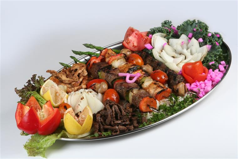 platter of kabobs with chicken, steak, and vegetables, tomatoes, greens, onion, peppers, and onion