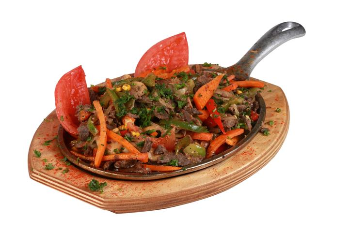 sliced meat on a skillet topped with peppers, carrots, tomatoes and garnish