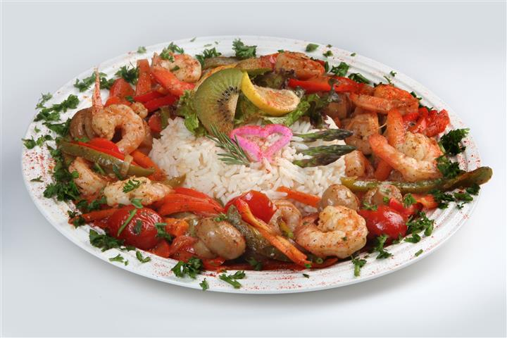 a bed of rice topped with garnish with grilled shrimp and vegetables