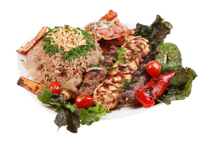 grilled chicen & steak skewers with a bed of rice, tomatoes, and peppers topped with garnish