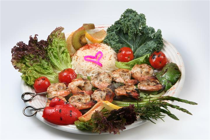 grilled shrimp skewers with a bed of rice with tomatoes and lemon wedges with pieces of lettuce
