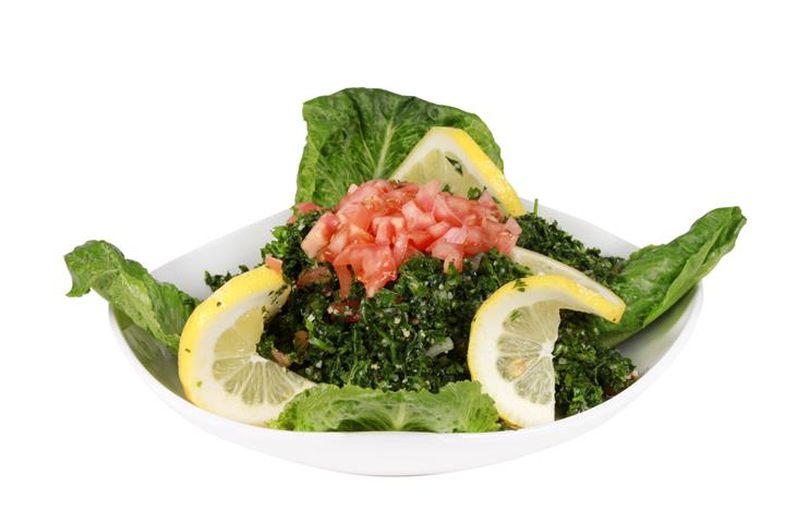 a bed of spinach topped with tomatoes with lemon slices over a bed of lettuce