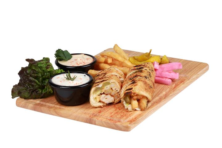 wrap fulled with chicken and french fries on a wooden board with a side of fries and 2 dipping sauces