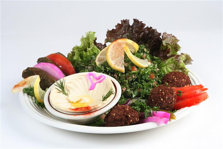 assortment of falfels with a side of hummus and a bed of lettuce