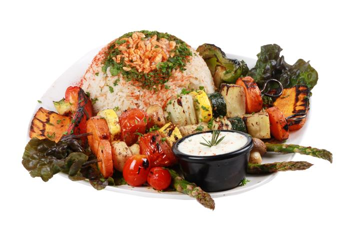 grilled chicken with veggies on a skewer with a bed of rice and a side of dipping sauce