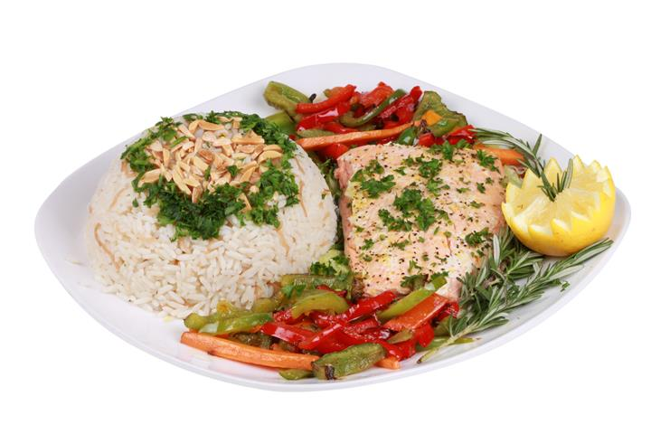 salmon with a bed of rice and veggies topped with garnish