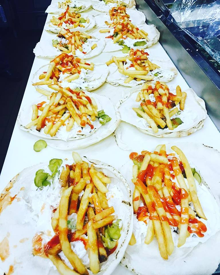 assortment of tortillas topped with fries covered in yogurt and hot sauce