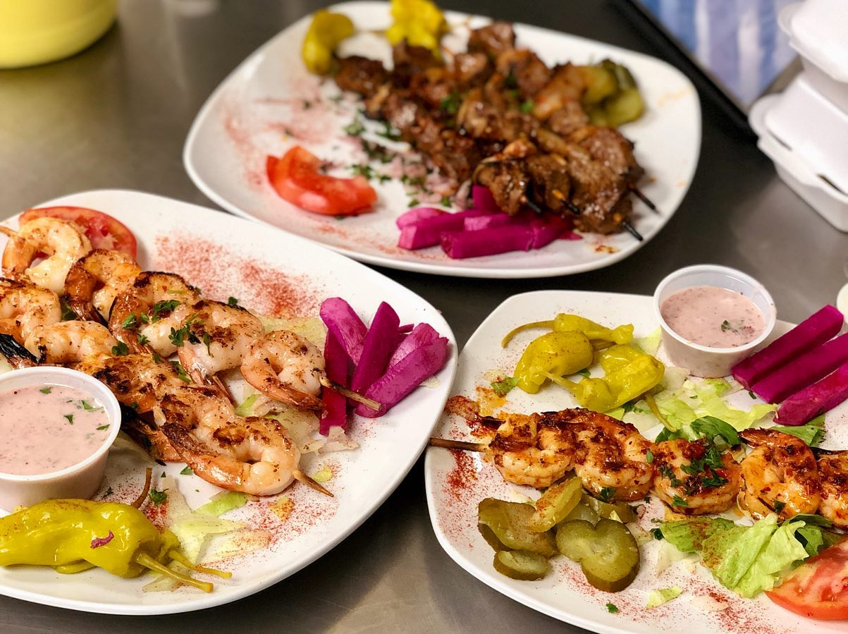 shrimp and meat skewers on plates topped with garnish