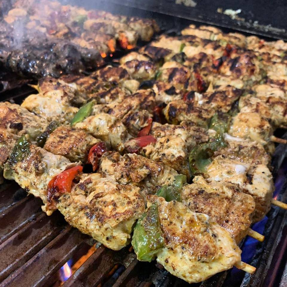 chicken shawarma on skewers on a grill with peppers