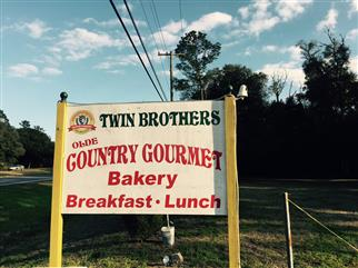 "sign that reads, ""Twin Brothers olde country gourmet bakery - Breakfast, Lunch"""