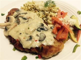 breaded meat in a mushroom sauce with side of vegetables