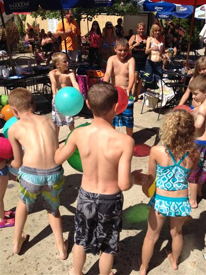 kids playing with plastic inflatable balls by the pool