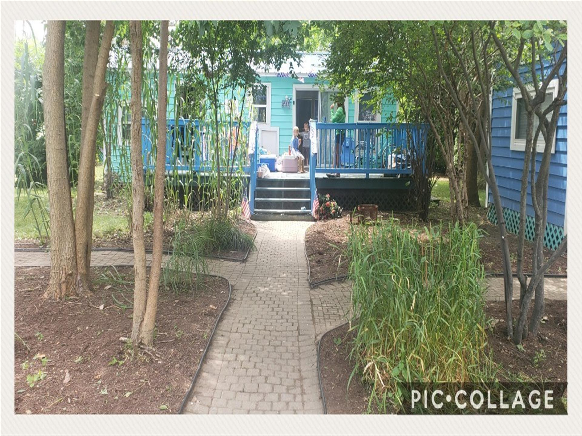 outdoor view of the path leading up to the teal house with bright blue staircase