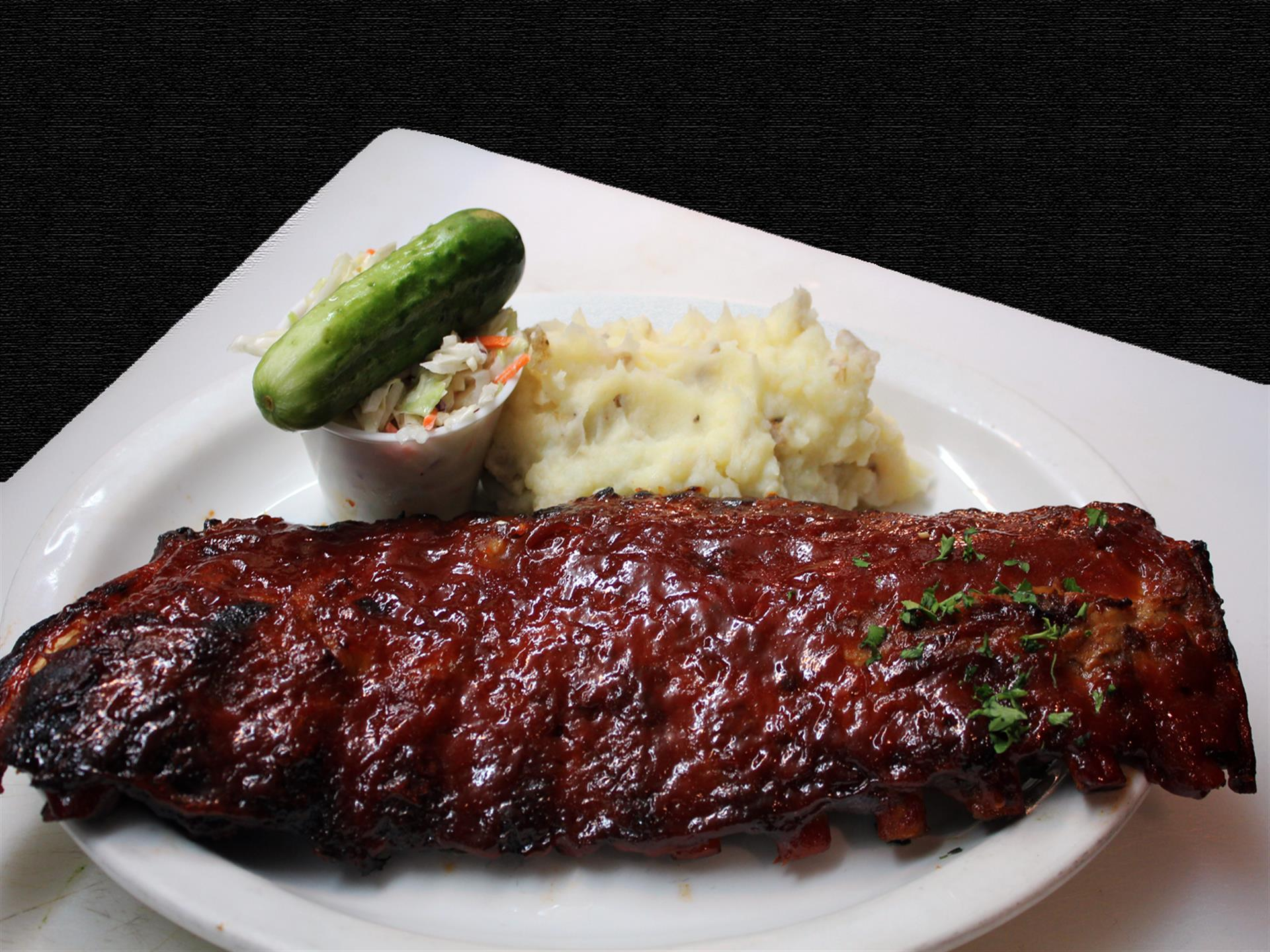 White plate of ribs, mashed potatoes, pickle, cole slaw