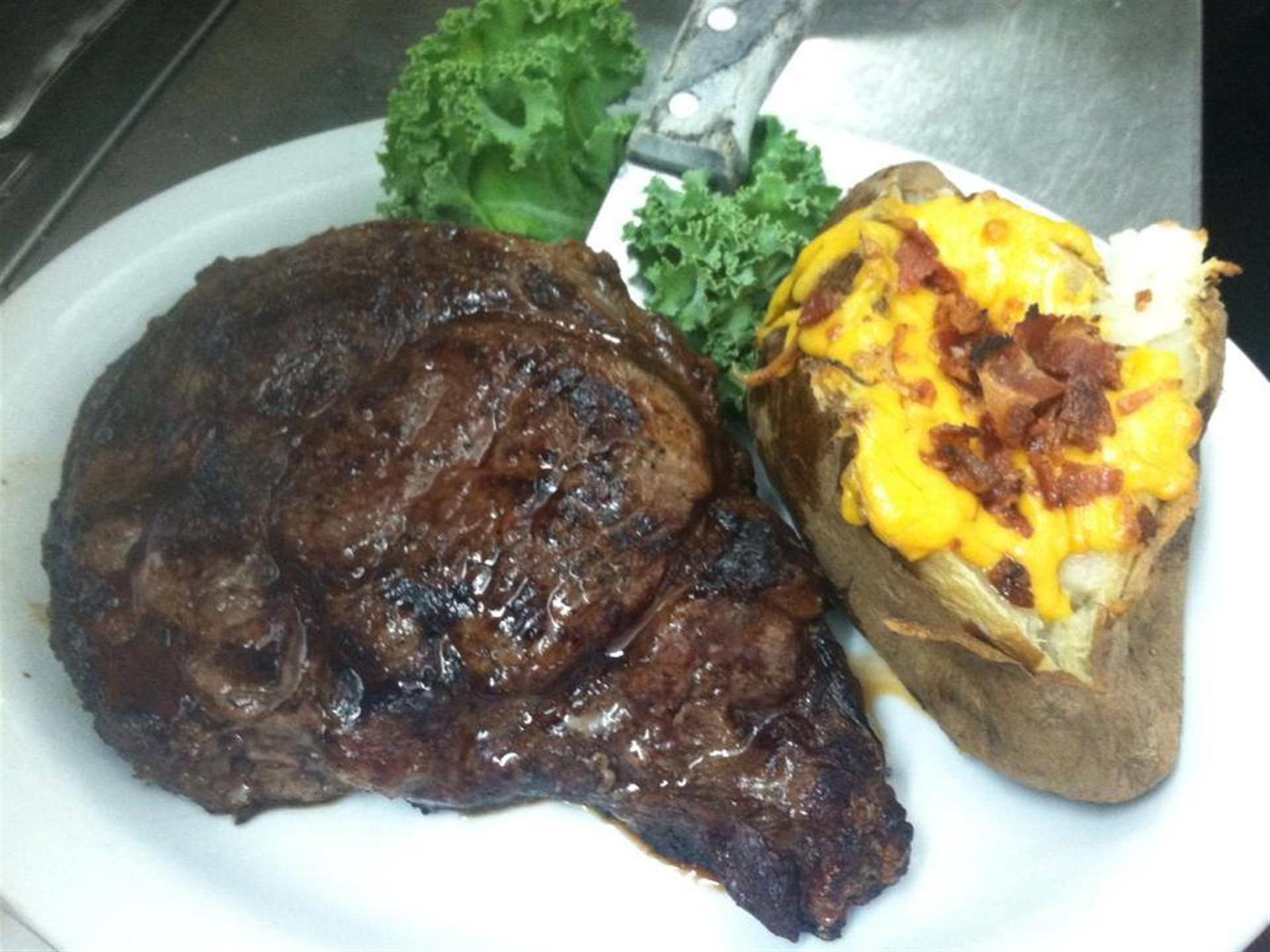 Steak and baked potato on white plate