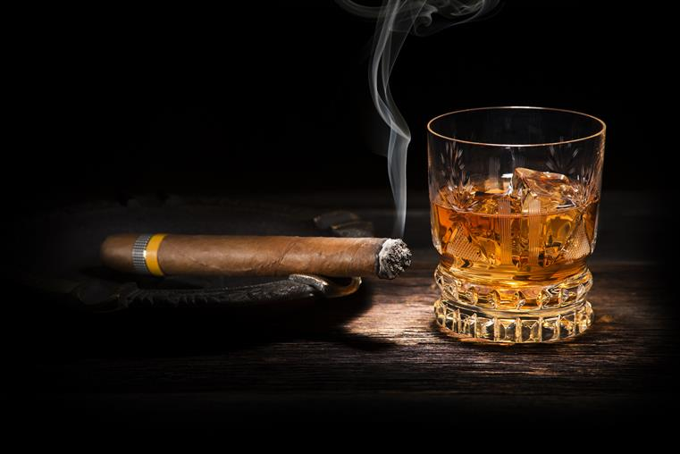 Lit cigar and alcoholic drink