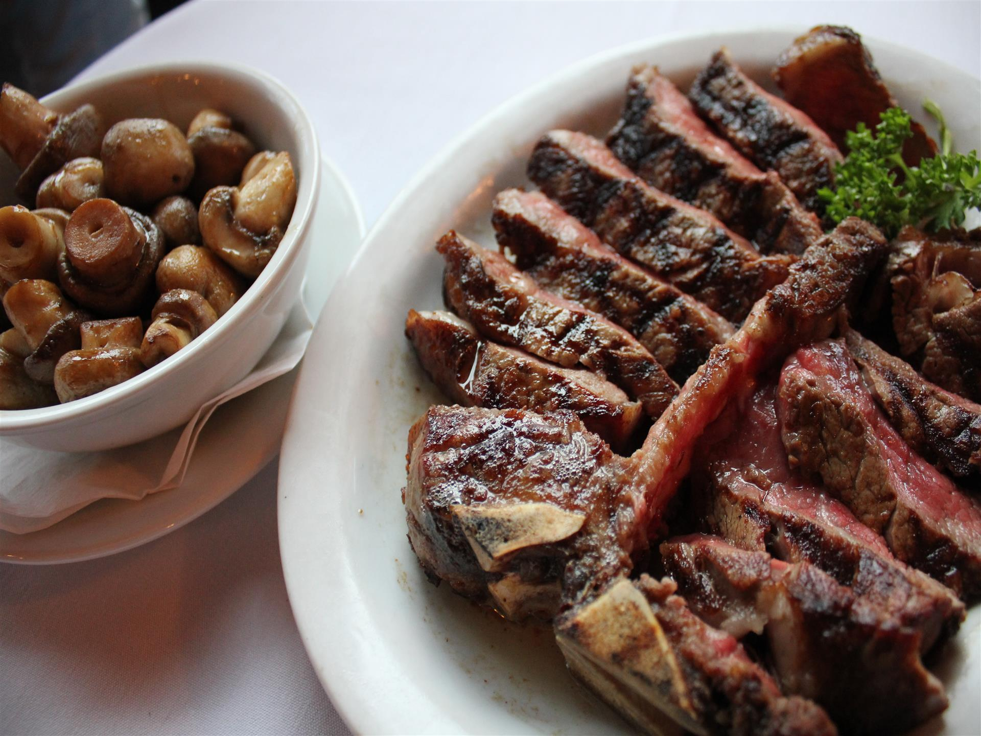 Sliced beef on plate with side of mushrooms