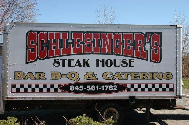 Schlesingers Steak House Barbecue and catering. 845-561-1762 on side of truck outdoors
