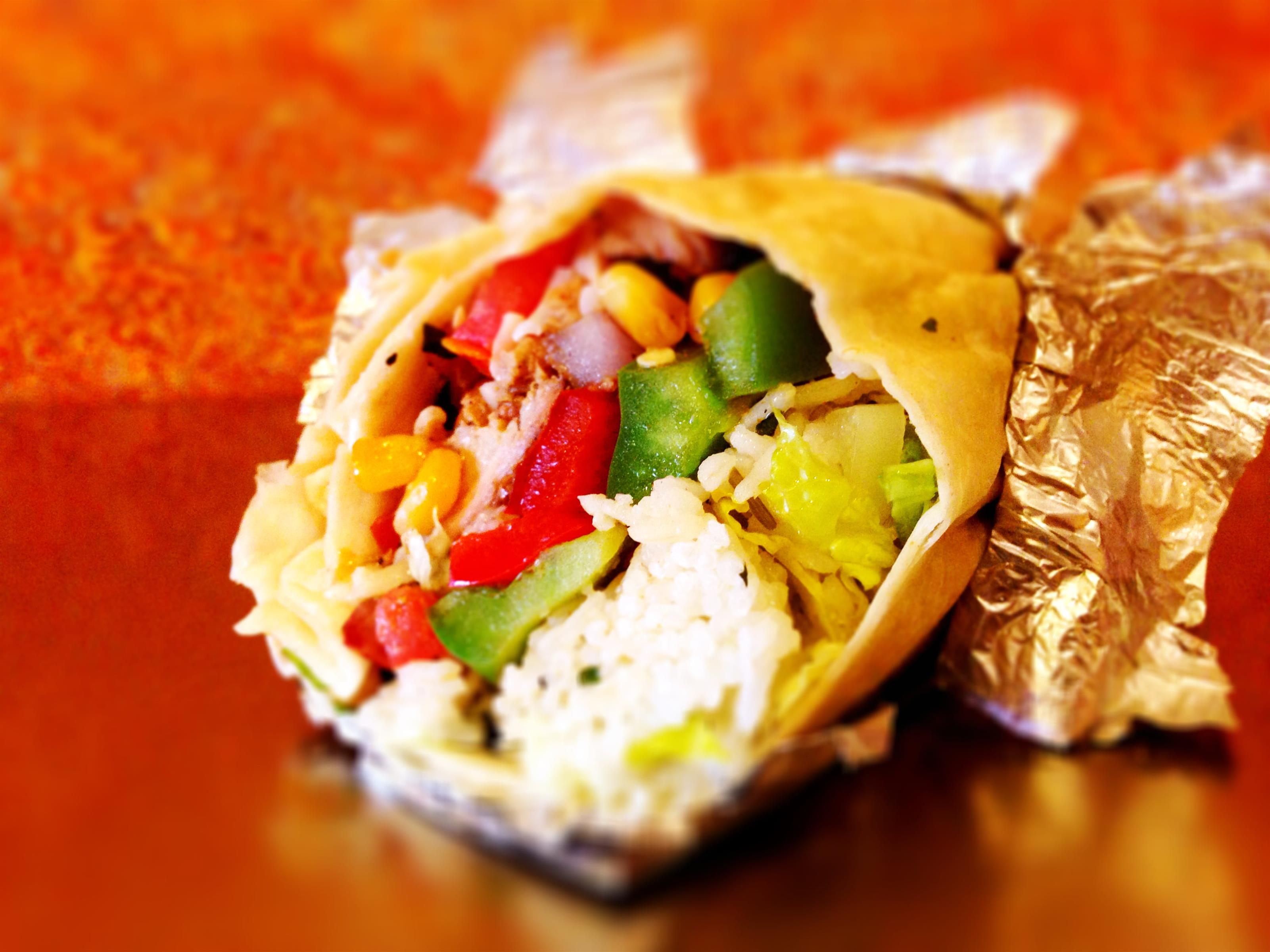 Burrito wrapped in aluminum foil filled with rice, peppers, corn and lettuce