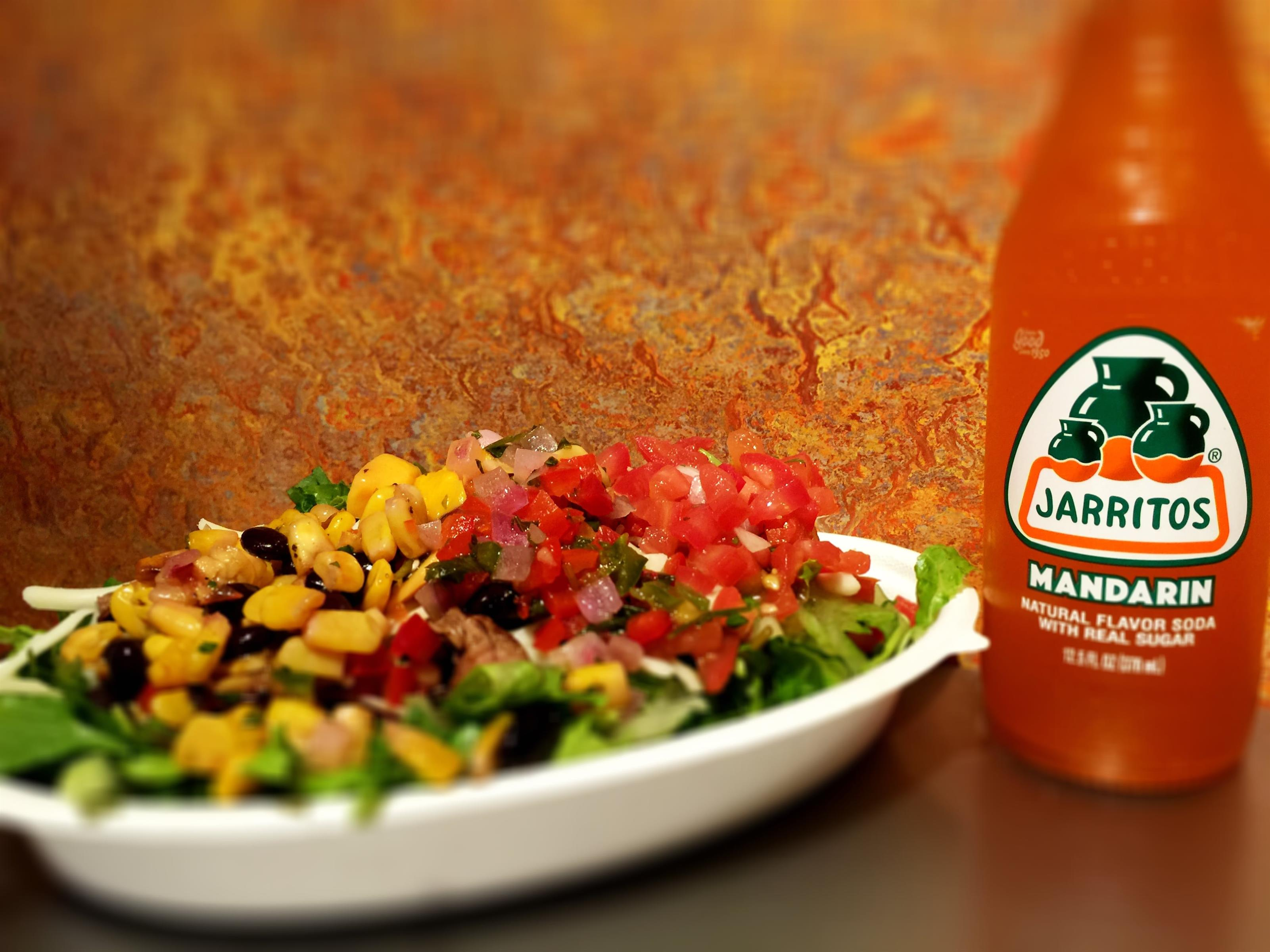 Bowl of rice topped with lettuce, corn, salsa, and meat next to a mandarin soda