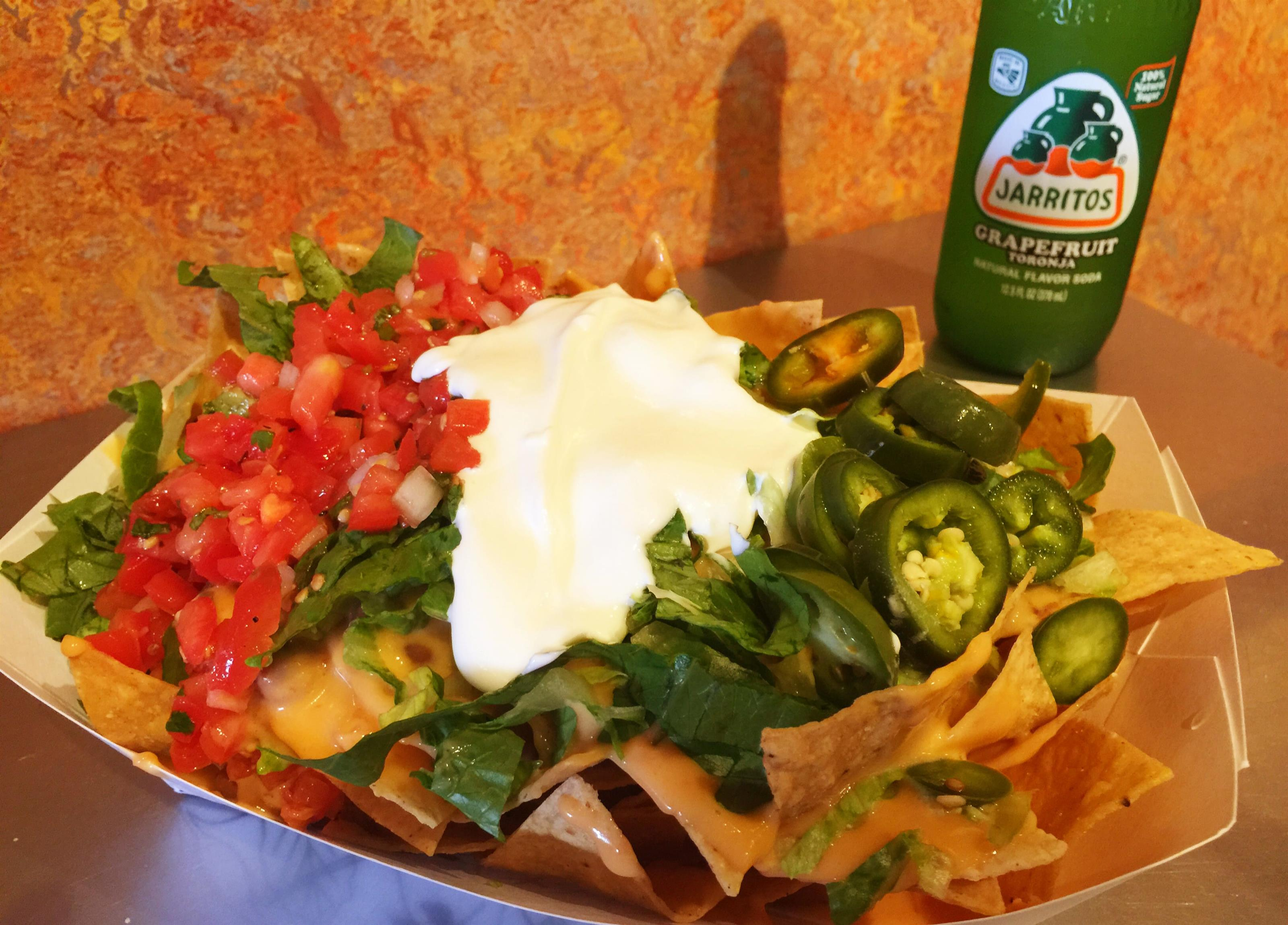Bowl of nachoes topped with lettuce, corn, jalapenos, salsa, and meat next to a grapefruit soda