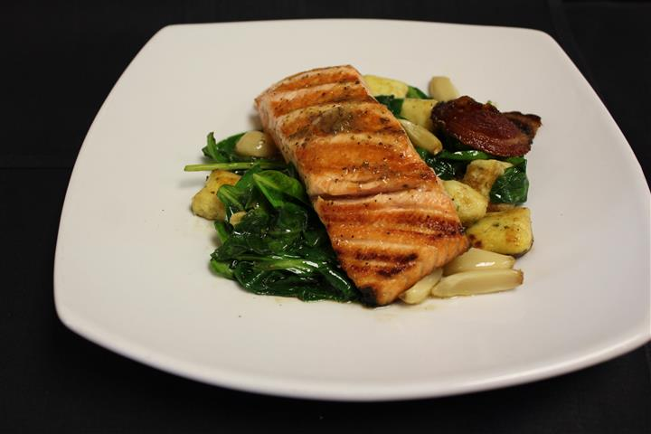 Grilled salmon served atop wilted spinach leaves